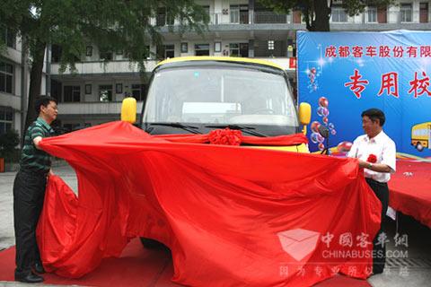 成客股份公司董事长王容坤同甘波校长一起为捐赠的专用校车揭幕