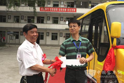 成客股份公司董事长王容坤向甘波校长转交专用校车钥匙