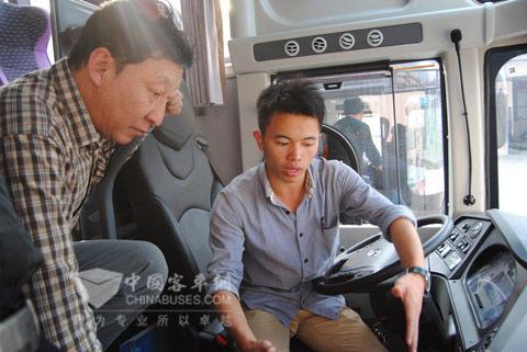 工作人员为长治汽运总经理张志斌(左)讲解龙翼车联网科技平台